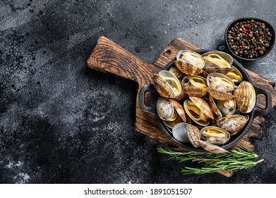 Cooked Clams vongole in a pan. Black background. Top view. Copy space.