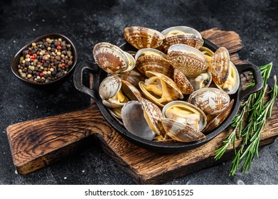 Cooked Clams vongole in a pan. Black background. Top view.