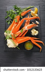 cooked Crab legs with melted butter, garlic cloves, lemon slices and fresh parsley on black stone tray, on wooden table, vertical view from above, close-up