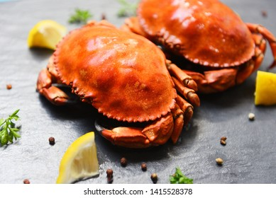 Cooked crab on dark plate with lemon herbs and spices / Seafood boiled red stone crabs salad