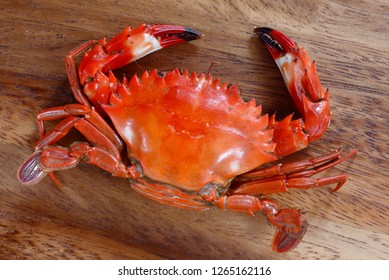 a cooked crab on  wooden plate, pile of cooked crabs