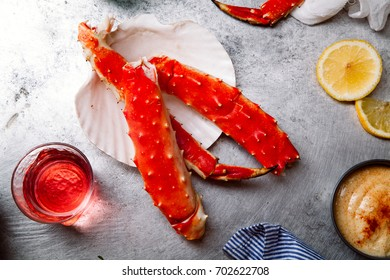 Cooked crab phalanx with aioli sauce and lemon slices on metallic background. Top view with copy space.