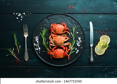 Cooked crabs with spices on a black background. Top view. Free space for your text.