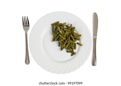 Cooked cut green bean on the white plate with fork and knife