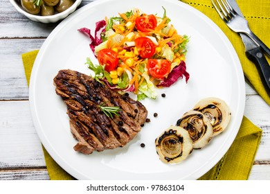 cooked cut of meat garnish with mixed salad