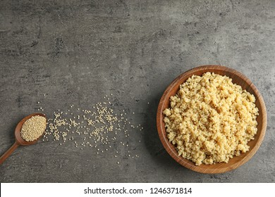 Cooked delicious quinoa in wooden bowl on table, top view. Space for text