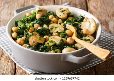 Cooked diet chickpeas with spinach and champignons close-up in a bowl on the table. horizontal