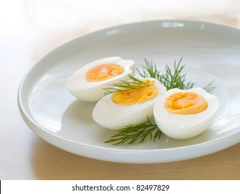 Cooked egg  on white plate with dill