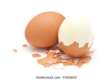 A cooked egg peeled and standing with eggshell pieces on white background.