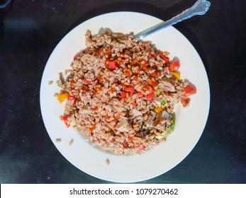 Cooked farro grains with pork and bell peppers.