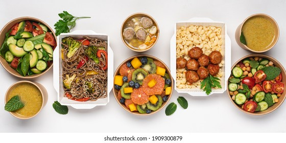 Cooked food in paper eco-friendly containers on white background. Food delivery for home or office. Vegetable, fruit salads, soups, meat and side dishes