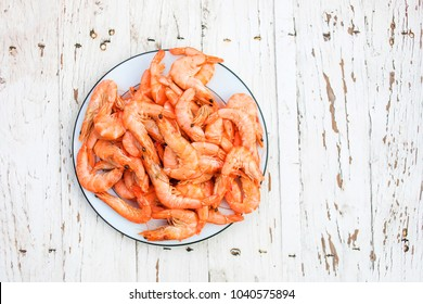 Cooked fresh  shrimps on a white plate over old white wooden table with copy space, flat lay. Seafood healthy food concept