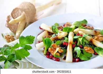 Cooked fresh white asparagus on lamb's lettuce with candied walnuts, pomegranate seeds and balsamic vinegar