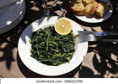 Cooked greens salad served with lemon and olive oil on a white dish next to bread, plates on wooden table in greek tavern. Horizontal. Daylight. Hard shadows. Outdoor.