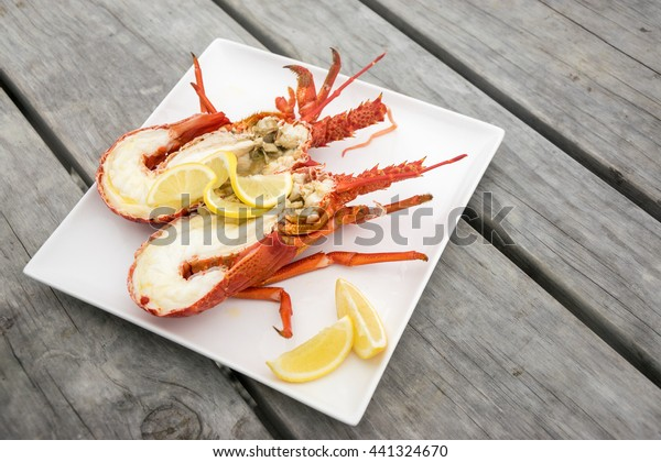 Cooked and halved New zealand crayfish on the wooden table.
