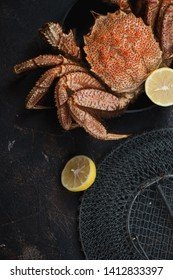 Cooked horsehair crab or hairy crab with lemon, top view over dark brown stone surface, vertical shot