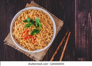 Cooked instant noodles in bowl with chopsticks in top view closeup on wooden table with copy space