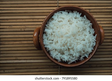 Cooked Jasmine rice in Bowl on bamboo mat.