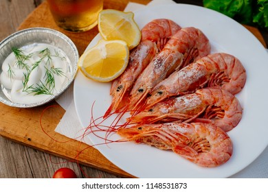 Cooked langoustines on a white plate served with white sauce, lemon and cold drink in a street cafe