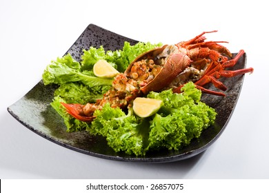 cooked large lobster in a bowl with lettuce and lemon