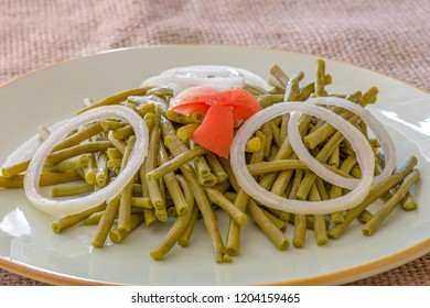 Cooked long Chinese green beans. Delicious salad that only uses oil and vinegar as dressing. The plate is garnished with a star of tomato and white onion rings.