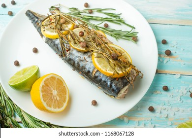 Cooked mackerel on a white plate with spices, herbs, lemon, lime and salt. A large plan