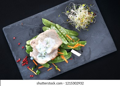 Cooked meat on a sweet pea salad served with white yoghurt sauce.