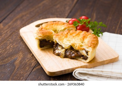 Cooked meat pie cut in half on a wooden cutting board