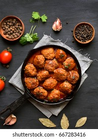 Cooked meatballs in frying pan on black background, top view