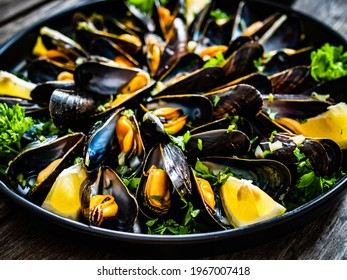 Cooked mussels with lemon and parsley on wooden table