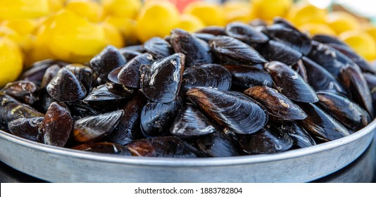Cooked Mussels. Mussels in lemon sauce. Sea products. Mussel shop, mixed type mussel and mussel stand with lemons.