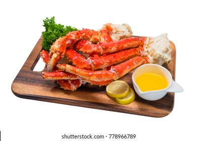 Cooked Organic Alaskan King Crab Legs with Butter and lemons,Alaskan King Crab on wood plate in white background.