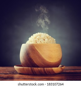 Cooked organic basmati brown rice in wooden bowl with hot steam smoke on dining table. Low light setting with retro revival style.