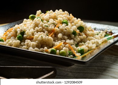 Cooked pearled barley porridge with green peas and grated carrots