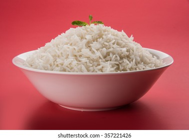 cooked plain white basmati rice served in a ceramic bowl or plate, isolated over colourful or wooden background