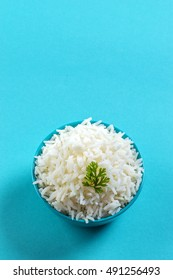 Cooked plain white basmati rice with corriander in a blue bowl on blue background
