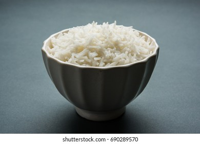 cooked plain white basmati rice served in a ceramic bowl, isolated over colourful or wooden background