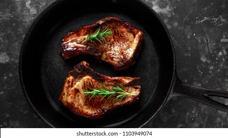 Cooked Pork Loin chops in rustic skillet, pan with rosemary. top view. background
