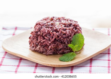 Cooked purple rice berry in wooden plate with peppermint leaves; clean food; healthy eating.