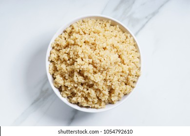 Cooked quinoa in white bowl, top view