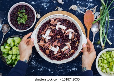 Cooked red beans with wine, mushrooms, herbs and spices. Woman hands holds vegetarian lunch, vegan dinner, healthy food. Top above view