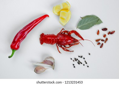 Cooked red crayfish or crayfish  with red hot pepper, lemon, bay leaf and garlic on white background. Food minimalism concept.