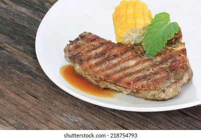 Cooked rib-eye Beef steak on a wooden table.