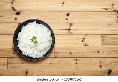 Cooked rice in bowl on wooden table. Top view and Copy space