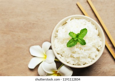 Cooked rice in a bowl on wooden table background