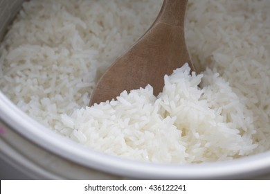 Cooked rice on wooden ladle in electric rice cooker.