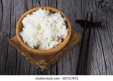 Cooked rice with peppermint in wooden bowl on a wooden table, Thai food rustic style