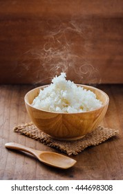 cooked rice with smoke in wooden bowl on wooden background,hot cooked rice in bowl