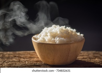 Cooked rice with steam in wooden bowl on dark background,hot cooked rice in bowl selective focus,soft focus
