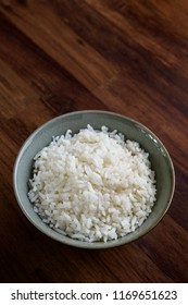 Cooked rice in vintage ceramic bowl on wood table